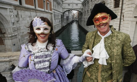 A masked couple poses in front of the Bridge of Sighs in Venice,