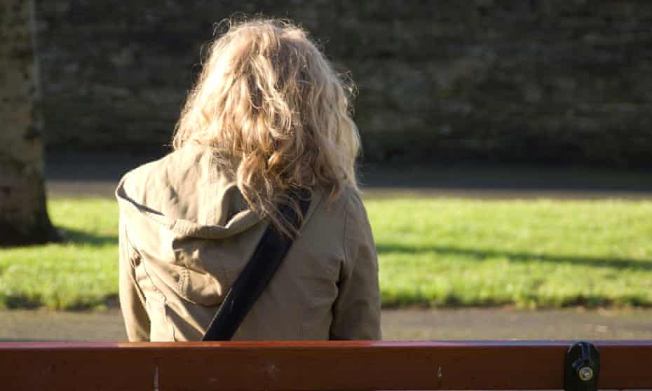 Young woman sitting on park bench facing away from camera