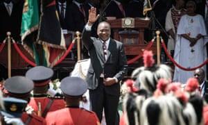 Uhuru Kenyatta waves to guards of honour after his arrival to take oath of office at Kasarani stadium in Nairobi.