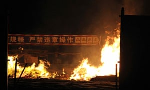 """Flames rise as a banner in the background reads """"no illegal operations"""" at the site of a series of explosions"""