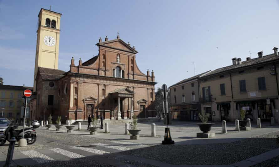 Two reporters stand in front of the San Biagio church in Codogno.