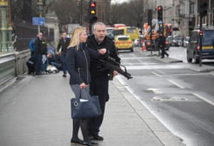 An armed police officer assists a woman on Westminster Bridge
