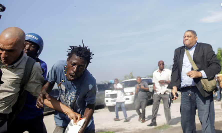 People run as Haiti's Senator Jean Marie Ralph Féthière holds a gun in Port-au-Prince, Haiti.
