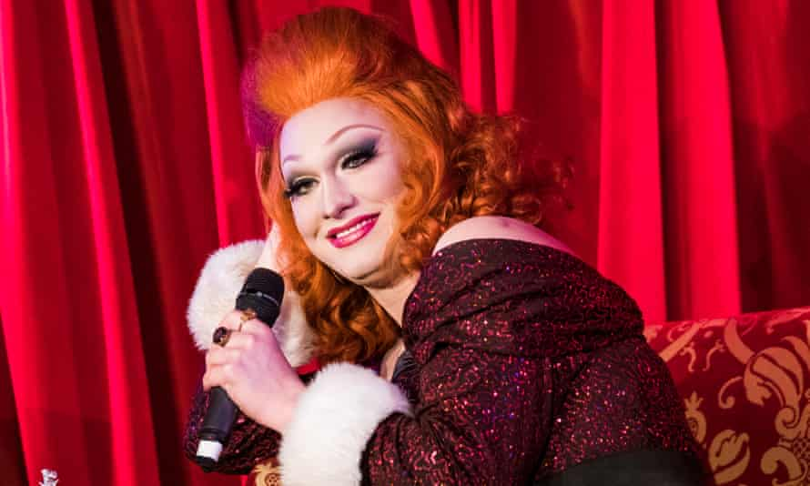 Jinkx Monsoon, heavily made up and with bright copper-coloured hair, on stage holding a mic, smiling and with a bright red curtain behind