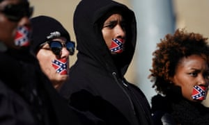 People stand in protest with Confederate flag stickers covering their mouths, outside the museum.