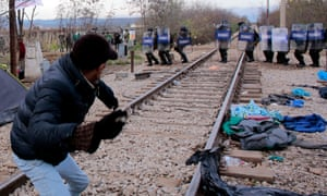 Migrants hurl stones at Macedonian policemen during clashes as the migrants protest against the building of a metal fence at the Greek-Macedonian border.