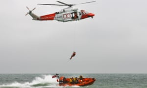 An independent rescue team member hanging from a winch, suspended from a helicopter with a boat in the sea below
