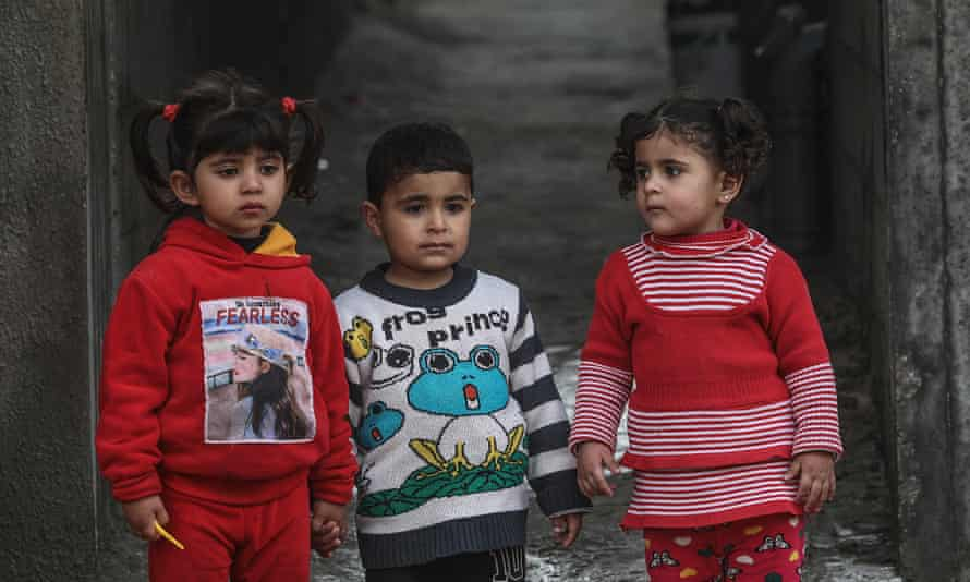 Children in the al-Nusairat refugee camp in central Gaza look on as the streets are sprayed with disinfectant as a precaution against the spread of Covid-19