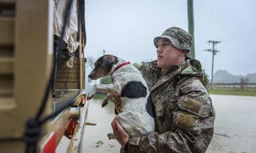 A member of the New Zealand Defense Force rescues a dog from floods as they assist a family with their evacuation near Ashburton in New Zealand's South Island, Sunday May 30, 2021. Several hundred people in New Zealand were evacuated from their homes Monday, May 31, 2021 as heavy rainfall caused flooding in the Canterbury region. (Corp. Sean Spivey/NZDF via AP)