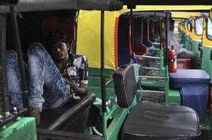 Delhi, India: An autorickshaw driver rests during a public transport strike