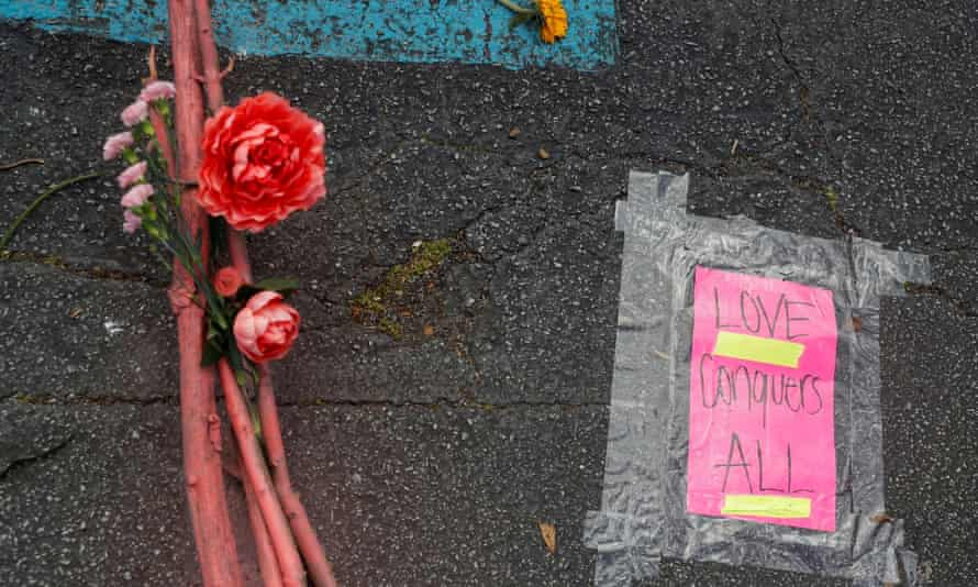 A placard taped to the ground is pictured next to flowers during a vigil at a makeshift memorial outside the Gold Spa following the deadly shootings in Atlanta, Georgia.