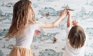 Two children holding a ship against a wallpapered wall