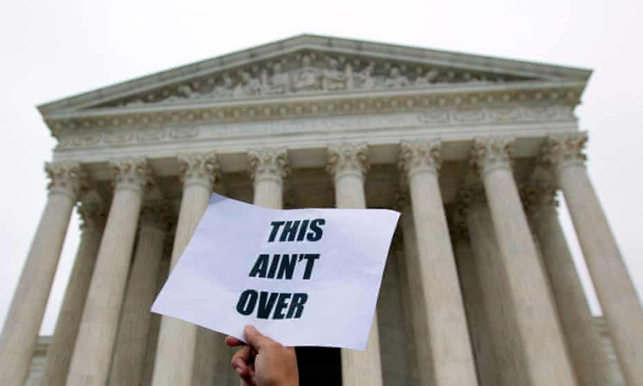 A demonstrator outside the US supreme court with a placard that reads: 'This ain't over'