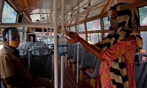 A women uses a sanitiser as she boards a bus in Chennai.