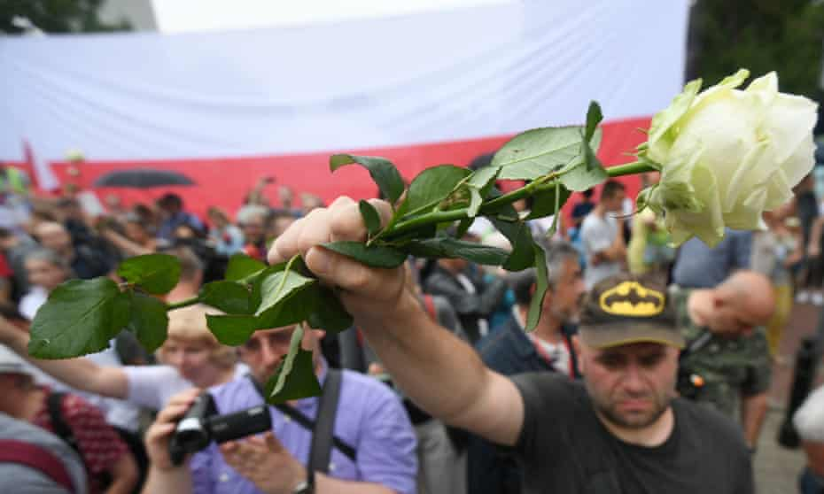 Protesters hold white roses