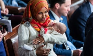 Ilhan Omar holds the child of the Democratic representative Eric Swalwell during Thursday's ceremonies.