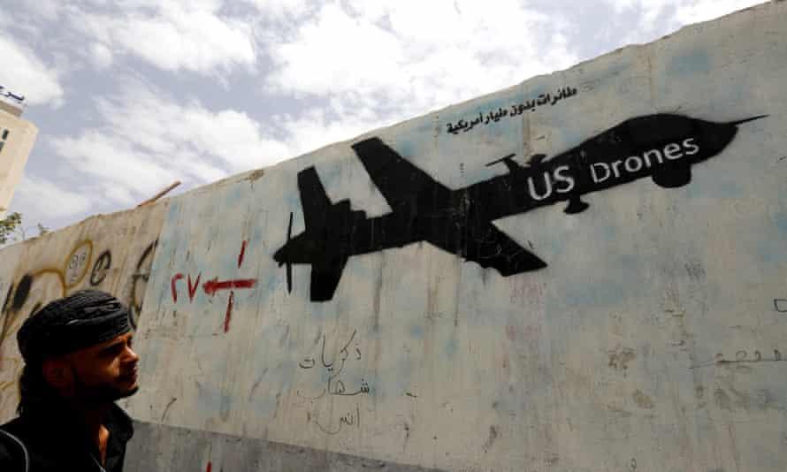 A Yemeni man looks at graffiti showing a US drone