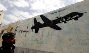A Yemeni man looks at graffiti showing a US drone after al-Qaida in Yemen confirmed the death of its leader in US drone strike, in Sana'a, Yemen, 16 June 2015.