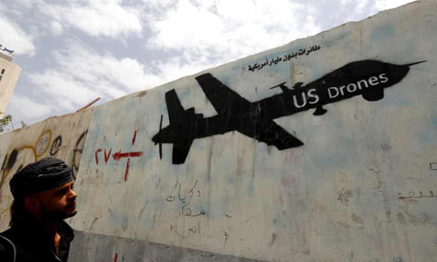 A Yemeni man looks at graffiti showing a US drone after al-Qaida in Yemen confirmed the death of its leader in US drone strike, in Sana'a, Yemen, 16 June 2015.