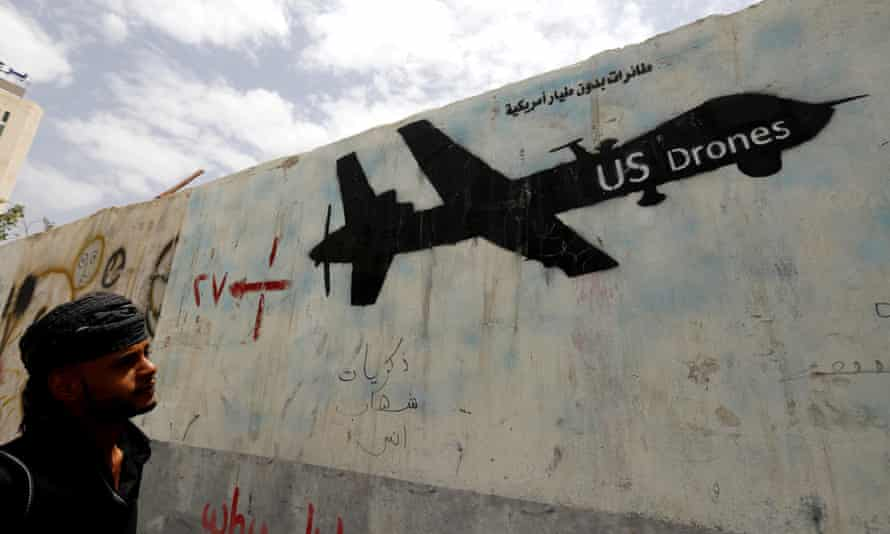 A Yemeni man looks at graffiti showing a US drone after al-Qaida in Yemen confirmed the death of its leader in a US drone strike in June.