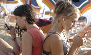 Two teenage girls plugged into mobile phones at the beach