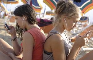 Teenage girls, 13 years using smartphones at the beach.