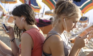two girls listening to their music on smartphones on the beach