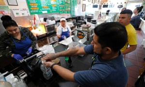 A customer uses sanitizer before picking up his order at Las Compadres Taqueria in Oakland, California.