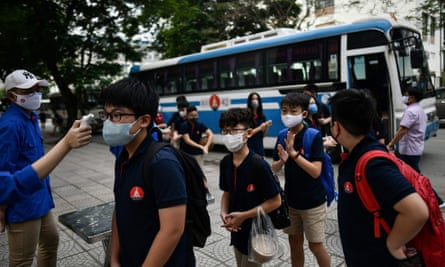 Children wearing face masks wait to be tested as they return to a school in Hanoi.