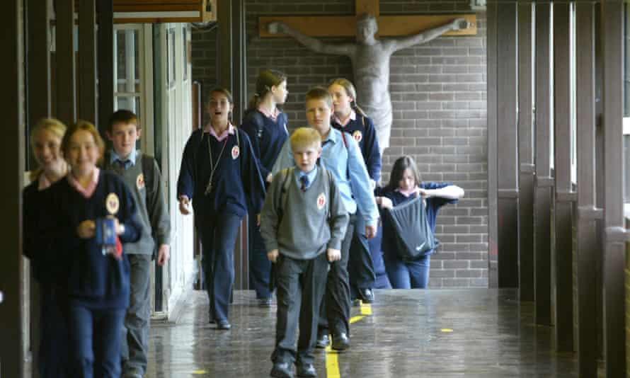 Pupils walk past a crucifix at a Catholic school.