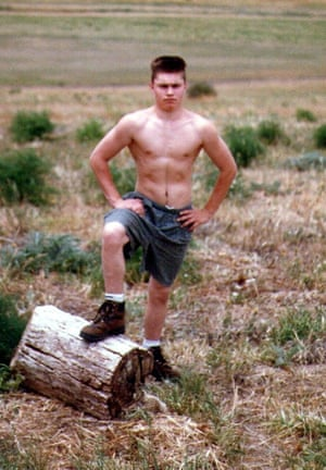 Jason Whiter, at 18 with a short cropped haircut, stands shirtless outside, looking tough, with a knee up on a log.