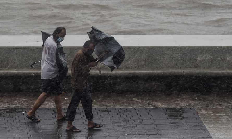 Two men carrying umbrellas walk on the Marine Drive under heavy rain in Mumbai.