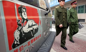 Chinese soldiers walk past a car sticker showing the map of China and Taiwan and the words 'We must liberate Taiwan'.