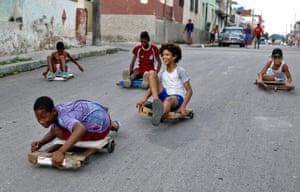 Havana, CubaChildren race their 'Chivichanas', hand-made trolleys along a street in the capital.