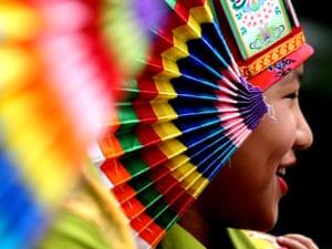 An exiled Tibetan folk artist wearing traditional Tibetan costume waits for the arrival of the Dalai Lama in Bangalore, India