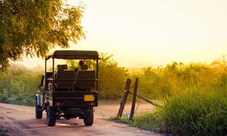 An open topped jeep carries tourists into the national park of Udawalawe, Sri Lanka to search for wildlife in the park