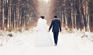 Back of bride and groom walking down a snow covered wooden path holding hands