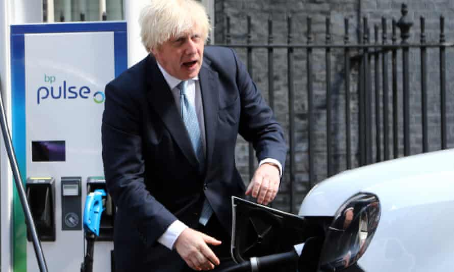 Boris Johnson plugging in an electric car to charge it up while apparently talking to someone off camera