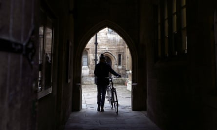 A student pushes a bicycle through an archway at Trinity College, part of the University of Cambridge.