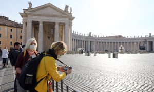 People stand behind barriers in an empty St Peter's Square in Rome. The aim of flattening the curve is to avert a situation such as in Italy which has been overwhelmed by a spike in cases.