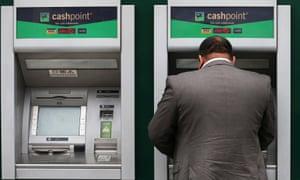 a man uses a Lloyds band cash machine