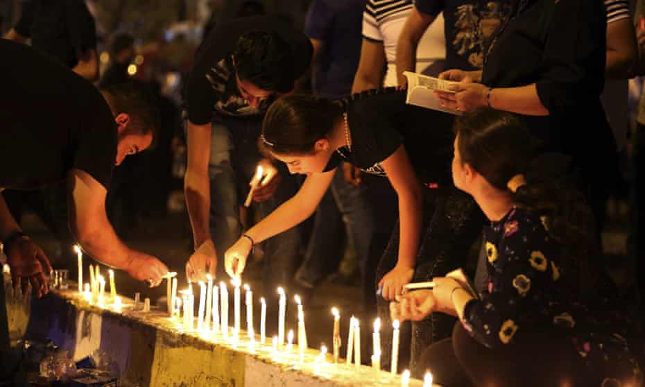 People light candles at the scene of a massive suicide truck bomb attack in Karada, Iraq.
