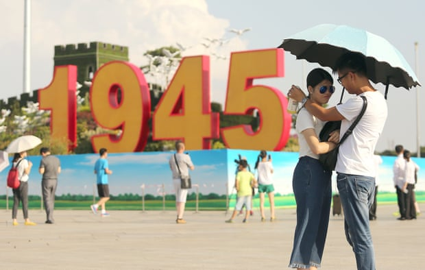 Chinese tourists visit Tiananmen Square, which is being decorated for the upcoming military parade on 3 September.