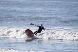 Porthcawl, Wales A surfer rides a wave at Sandy Bay