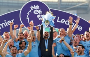 Guardiola lifts the trophy.