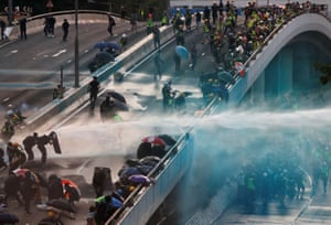 Riot police spray protesters with water cannon near the central government complex