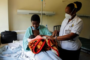 Secondary school student Jackline Bosibori, 17, is shown by a nurse how to breastfeed her one-day-old baby at Kenyatta National Hospital in Nairobi