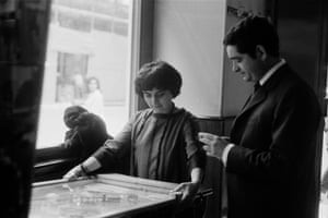 Varda at the Cannes Film Festival plays pinball with husband, director Jacques Demy in 1962