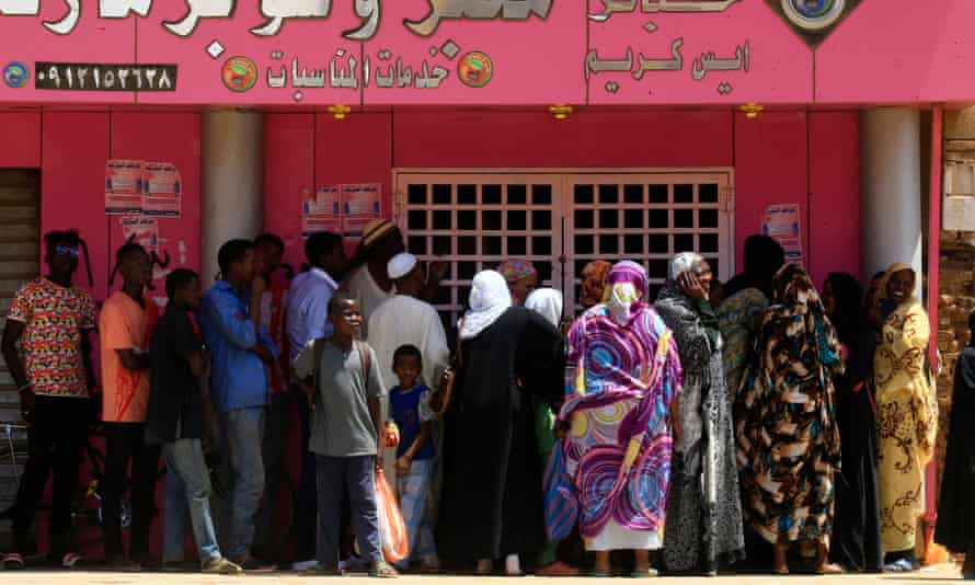 Sudanese people queue up outside a bakery