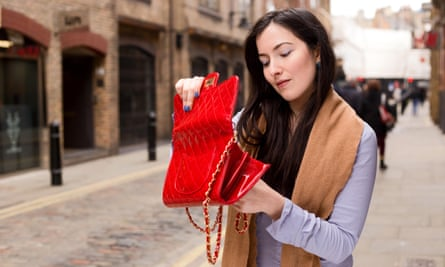young woman looking for something in her handbag